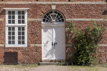 transom: Entrance in a historic building of red brick with a white front door, transom windows and a climbing rose, typical in Northern Germany