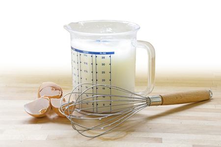 stirrer: beaten stiff egg white in a plastic jug, hand whisk and empty eggshells on a wooden plate, copy space