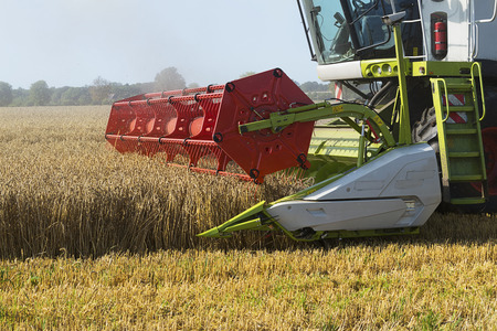 agriculture machinery: Dassow, Germany, August 13, 2015: part of a combine harvester working on a wheat field Stock Photo