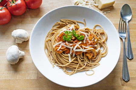 rustic wholemeal spaghetti with sauce of tomatoes, mushrooms and Parmesan cheese on a wooden table