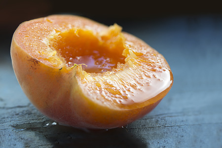 juice fresh vegetables: halved apricot, ripe and juicy on blue wood, closeup with selected focus and narrow depth of field Stock Photo