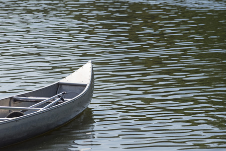 prow: prow of a canoe on the water with small glittering waves, copy space Stock Photo