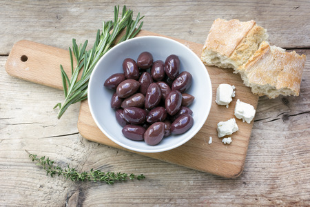 provence: Kalamata black olives in a white bowl, bread, feta cheese and herbs garnish on a rustic wooden table, view from above