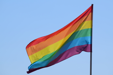 sex discrimination: rainbow flag against the blue sky, symbol of tolerance and acceptance, diversity, hope and longing. The colors of this flag are specially for LGBT (Lesbian, Gay, Bisexual, Transgender) Pride.