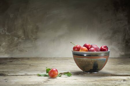 ambiente: wild red plums in a pottery ceramic bowl on an old wooden table in front of a rustic wall, plenty of copy space Stock Photo