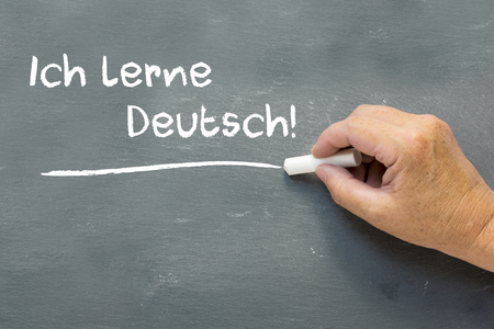 deutsch: Hand on a chalkboard with the German words Ich lerne Deutsch (I learn German). Language class concept showing student hand writing on the blackboard. Stock Photo