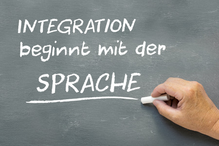 Hand on a chalkboard with the German words Integration beginnt mit der Sprache (Integration begins with the language). Language class concept showing teatcher hand writing on the blackboard.