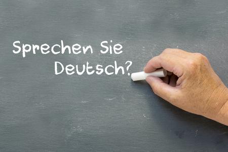 deutsch: Hand on a chalkboard with the German words Sprechen Sie deutsch (Do you speak German). Learning German, language class concept showing teacher hand writing on the blackboard. Stock Photo