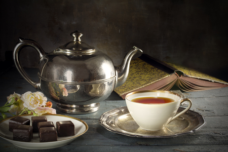 good old tea time, black tea in a porcelain cup, old-fashioned silver teapot, chocolate cookies and a good book on a rustic wooden table, copy space in the dark brown background Archivio Fotografico