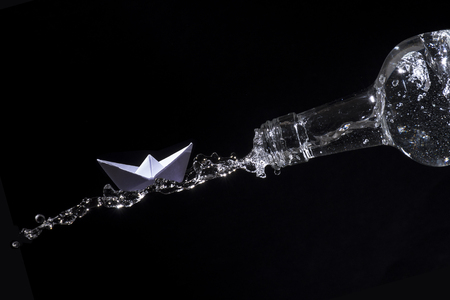 against the flow: Paper boat escape on a water splash out of a bottle against a black background, concept for get away, adventure or against the tide