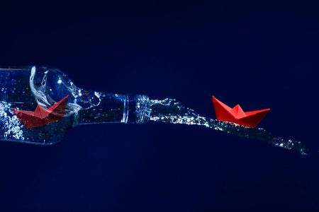 get away: Red paper boat rides on a water splash out of the bottle, another waits for freedom inside at the bottleneck, dark blue background, concept for get away, escape or liberation