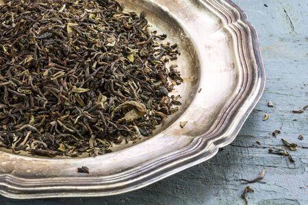 darjeeling: loose black Darjeeling Tea on a silver plate on rustic blue painted wood, closeup view from above