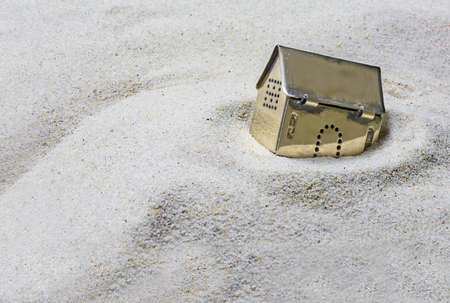 housing crisis: built on sand, small golden model house sinking into the sand, concept of risk in real estate financing, or investing in gold, selected focus, Copy Space