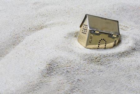 gebouwd op zand, kleine gouden model huis zinken in het zand, concept van risico's in de vastgoedfinanciering, of investeren in goud, geselecteerd focus, Tekstveld