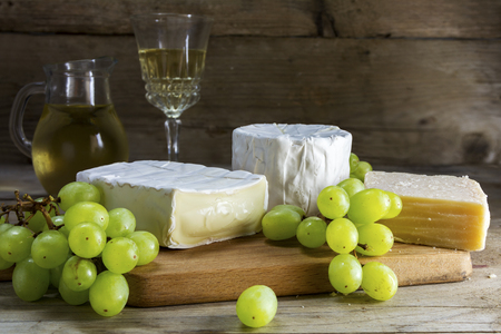 sorts: different cheese sorts with green grapes and white wine on rustic wood, selected focus, blurred dark wooden background