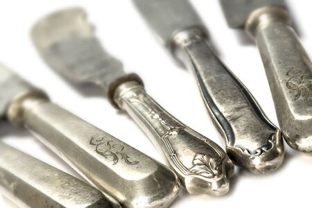 grunge silverware: old knifes made of silver on a white background, selected focus, very narrow depth of field