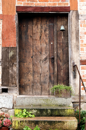 vintage door: old wooden front door made of planks in a historic half timbered house Stock Photo