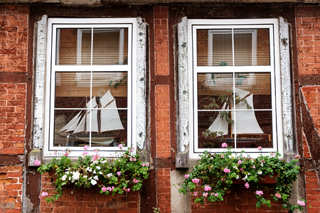 flower boxes: new mullioned windows with yacht model decoration and flower boxes in an old half timbered house