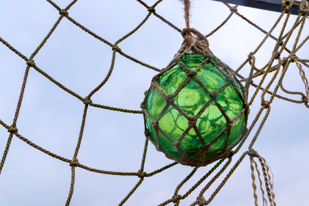 fishing float: Historical green glass fishing float ball with rope knots hanging in a fishing net to dry against the sky, used as floats on the nets by the fishermen Stock Photo
