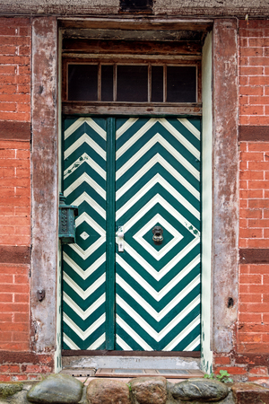 half timbered house: front door with green and white painted stripes in an old half timbered house, typical in northern Germany