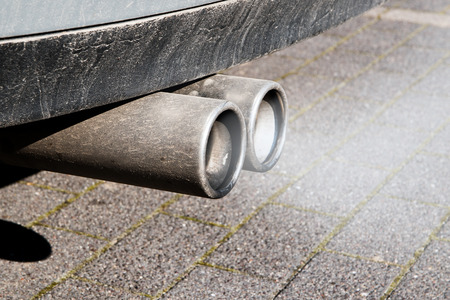 dirty: dirty dual exhaust pipes of a car, failed emission test