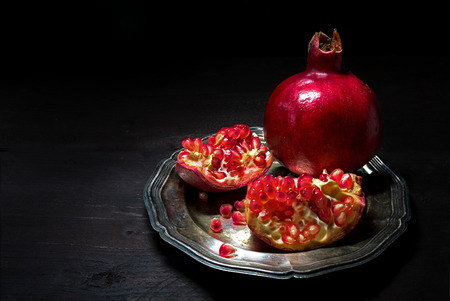 Pomegranate whole and broken up into pieces with grains on a silver plate on a dark wooden table, background fades from brown to black with copy space