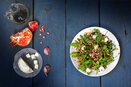 preparing salad with arugula, feta cheese, pomegranate, garlic and balsamic dressing served on a white plate on an old blue wooden table, view from above