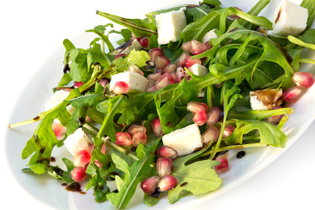 arugula: Fresh salad with arugula, feta cheese, pomegranate and balsamic dressing on a white plate Stock Photo