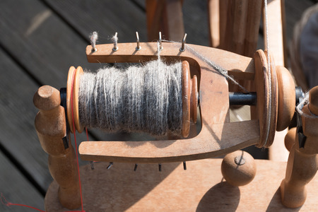 spindle and  spun wool yarnl, detail of a traditional wooden spinning wheel
