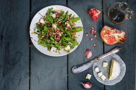 preparing salad with arugula, feta cheese, pomegranate, garlic and balsamic dressing served on a white plate on a rustic wooden table, view from above, copy space in the dark gray wood Standard-Bild