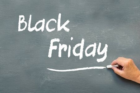 writing black: Hand writing Black Friday with chalk on a chalkboard, Black Friday sale concept Stock Photo
