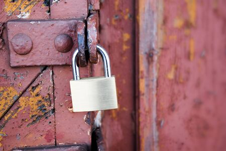 narrow depth of field: new padlock on an old red wooden gate, selected focus, narrow depth of field, copy space in the blurry background