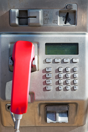 insertion: Public phone made from metal with  keypad, coin insertion, card slot and a red handset