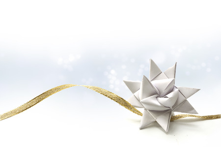 White paper star for Christmas decoration, also called Froebel or German star, with golden ribbon on a light blue background fading to white