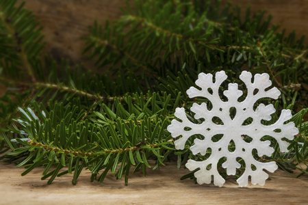 the snowflake: white snowflake star and fir branches on rustic wood as a Christmas decoration, copy space