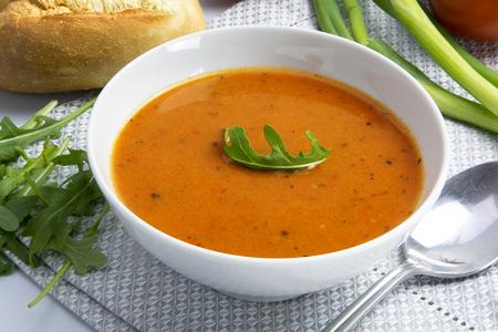 bread roll: Tomato cream soup in a white bowl with bread roll and arugula garnish Stock Photo