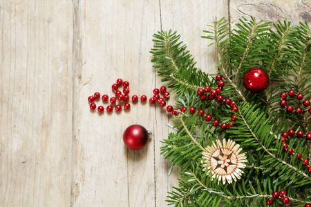 Fir branches with red  baubles and straw star on rustic wood as Christmas background with copy space