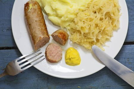 Bratwurst with sauerkraut, mashed potatoes and mustard on a blue wooden table, personal point of view, from above Stock Photo