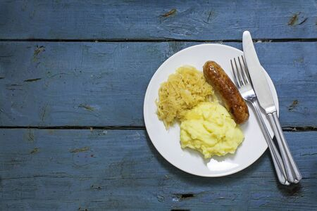 homestyle: Bratwurst with sauerkraut and mashed potatoes on a blue painted rustic wooden table, view from above, generous copy space