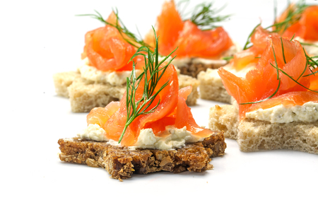 buffet: canapes in star shape with smoked salmon on horseradish cream and dill garnish for a cold buffet on Christmas or New Year, on a white background, selected focus, narrow depth of field Stock Photo
