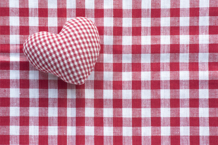 checked fabric: Cloth heart from small checked pattern fabric  in red and white on a background of a bigger checked pattern fabric, concept for Love, Mothers Day or Valentines Day Stock Photo