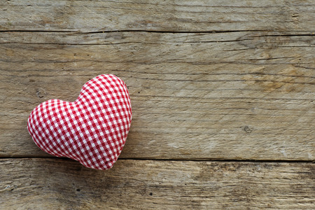 day valentine: heart made of cloth with red white checkered pattern on rustic old wood with copy space, concept of love at Christmas, Mothers Day or Valentines Day Stock Photo