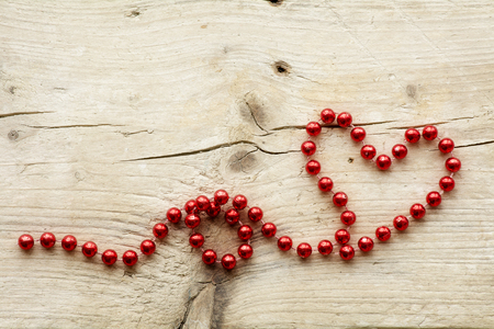 christmas beads: garland of red christmas beads forming a heart shape on a rustic light wood, love concept with copy space Stock Photo