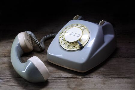 removed: old-fashioned telephone of gray plastic with rotary dial and removed receiver on a dark wooden table