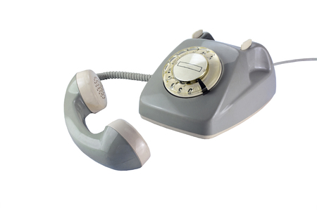 old fashioned rotary phone: Vintage rotary dial phone in gray with removed telephone receiver isolated on a white background Stock Photo