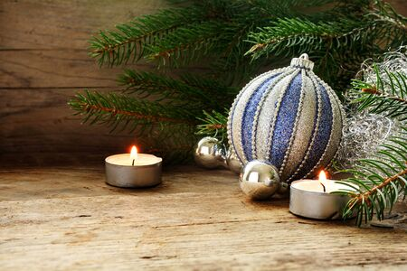 narrow depth of field: silver and blue baubles, fir branches and candles as Christmas decoration on warm rustic wood with copy space, selected focus, narrow depth of field Stock Photo