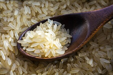 narrow depth of field: Wooden spoon in a heap of parboiled rice parboiled, closeup shot with selected focus and narrow depth of field.