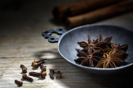 star anise christmas: Spices for Christmas baking, star anise, cinnamon and cloves on a rustic wooden table Stock Photo
