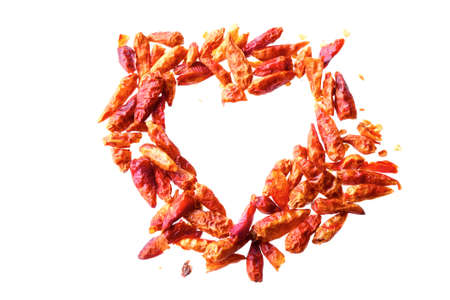 capsaicin: dried red chili peppers in a heart shape isolated on a white background, concept for heart health with capsaicin or hot love at Valentines Day