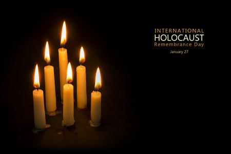 Six burning candles against black background